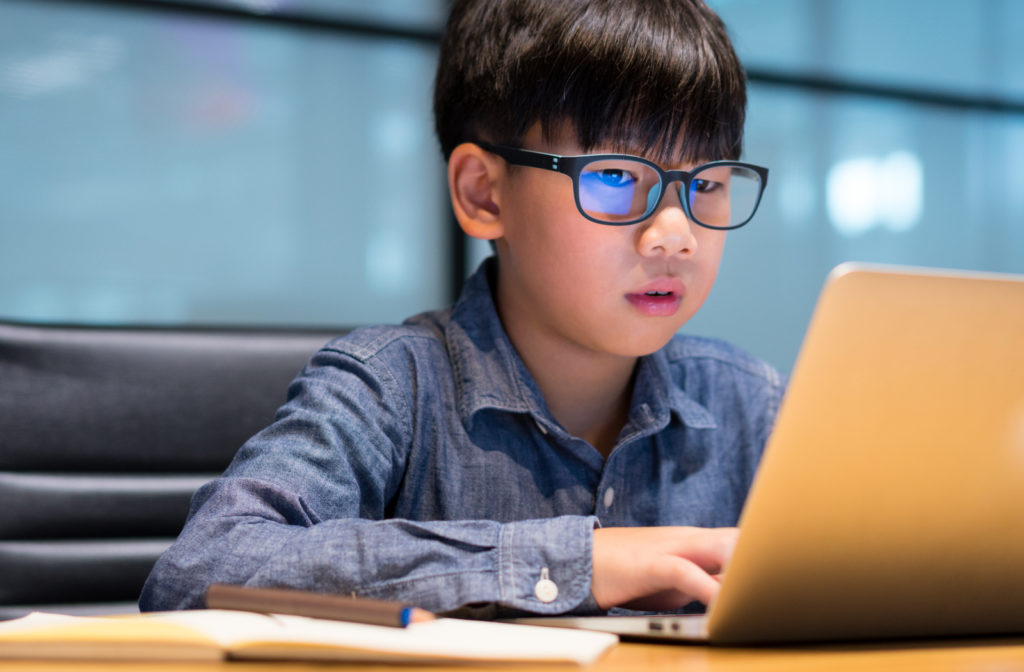 Young boy wearing blue light glasses while using laptop