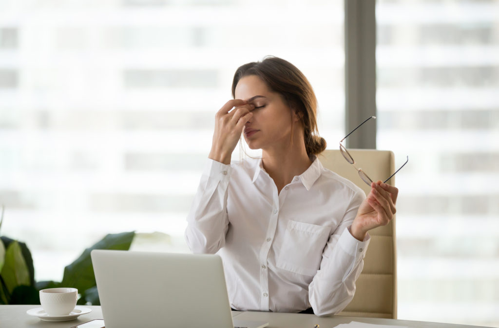 Young woman experiencing digital eye strain while using laptop